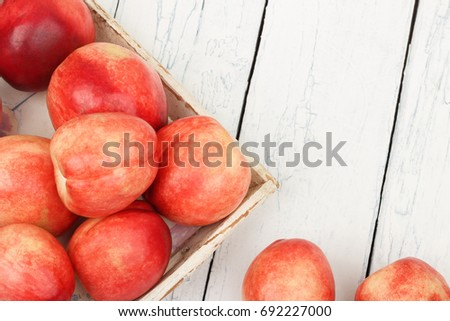 Ripe red peaches in the tray on the white wooden table, top view #692227000