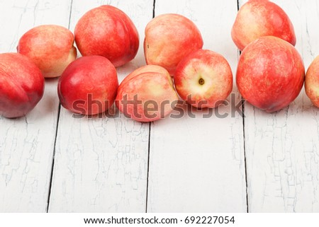 Ripe red peaches on the white wooden table, soft focus background #692227054