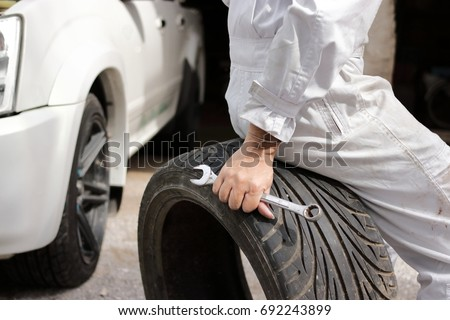 Selective focus on hands of professional mechanic in uniform sitting on tire and holding wrench at the repair garage background. #692243899