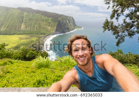 Selfie tourist man hiker taking self-portrait picture at Waipio Valley lookout in Big Island, Hawaii. Male backpacker smiling at camera phone on adventure nature travel.