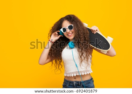 Curly haired teenage brunette girl wearing sunglasses headphones holding cruiserboard smiling. #692401879