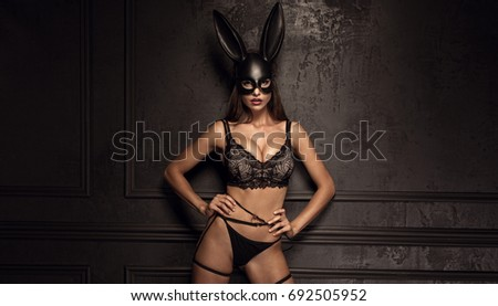 Sexy woman with large breasts wearing a black mask Easter bunny standing on a black background and looks very sensually #692505952