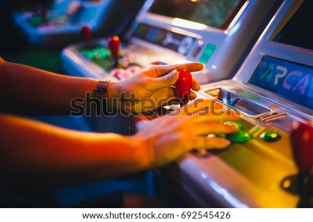 Detail on Hands with Arcade Joystick Playing Old Arcade Video Game Royalty-Free Stock Photo #692545426