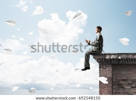 Young businessman sitting on building top with smartphone in hands #692548150