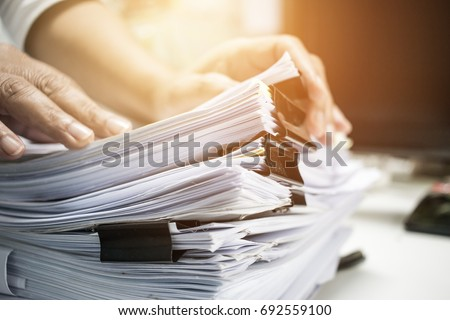 Work from Home, Businessman hands working in Stacks of paper files for searching information on work desk home office, business report papers,piles of unfinished documents achieves with clips indoor. Royalty-Free Stock Photo #692559100
