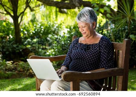 Senior woman using laptop in the garden #692560894