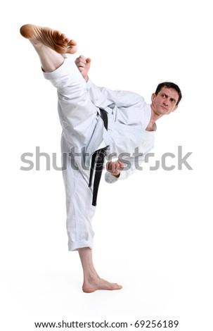 Karate. Man in a kimono hits foot on the white background #69256189