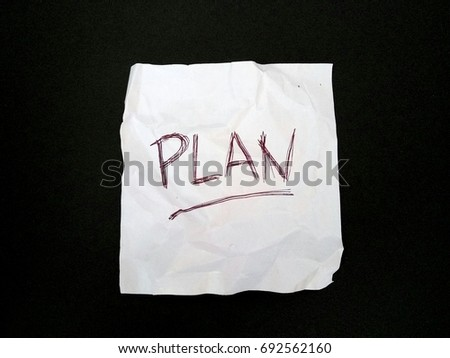 Plan written in a piece of paper on black background #692562160