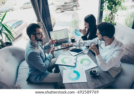 Presentation of a new start up for investors. Three young successful people are discussing numbers in a nice light modern coworking, all in formal wear, concentreted #692589769