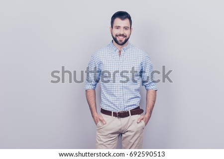 Success concept. Stylish young smiling bearded brunet is standing on pure gray background. He looks so classy! in smart casual outfit, his hands are in pockets #692590513