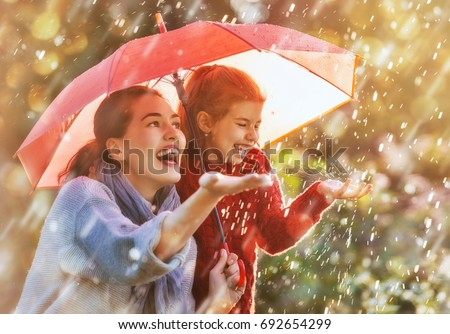 Happy funny family with red umbrella under the autumn shower. Girl and her mother are enjoying rainfall. Kid and mom are playing on the nature outdoors. Walk in the park. Royalty-Free Stock Photo #692654299