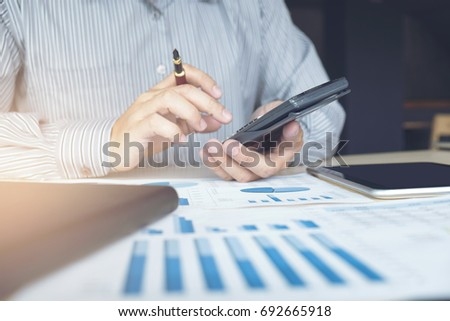 Business man or accountant working Financial investment on calculator with calculate Analyze business and market growth on financial document data graph and tablet, Accounting, Economic, commercial. #692665918
