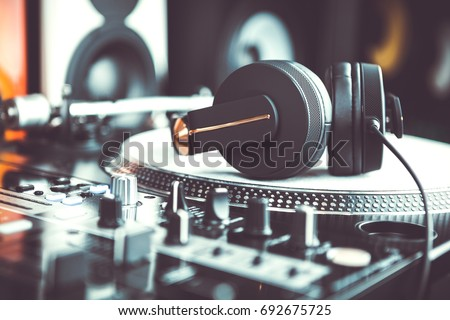 Big black dj headphones for professional disc jockey.listen to the music in high quality.Club djs headset with powerful bass.Retro audio equipment for sound recording studio.Vintage turntable player Royalty-Free Stock Photo #692675725