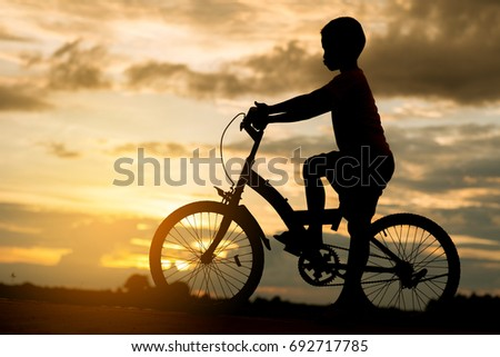 boy on bicycle with sunset bacground.silhouette litle boy on bike #692717785