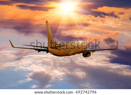 Commercial airplane flying above clouds in dramatic sunset  #692742796
