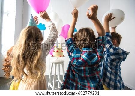 back view of cute cheerful kids reaching to birthday cake #692779291