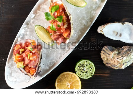 Delicious red fish in the shells of shellfish. With lemon and lime #692893189