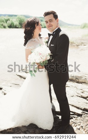 Elegant gentle stylish groom and bride near river with stones. Wedding couple in love #692919244