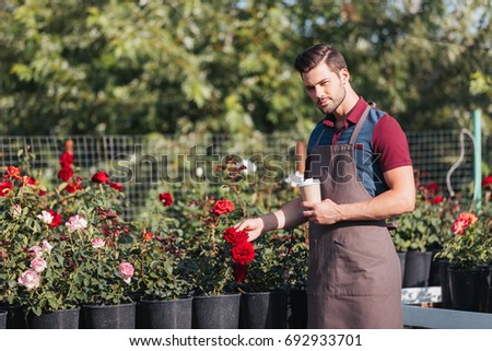 portrait of handsome gardener in apron holding disposable cup of coffee in garden #692933701