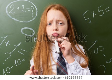 Red-haired schoolgirl on background of blackboard in classroom                                #692935537