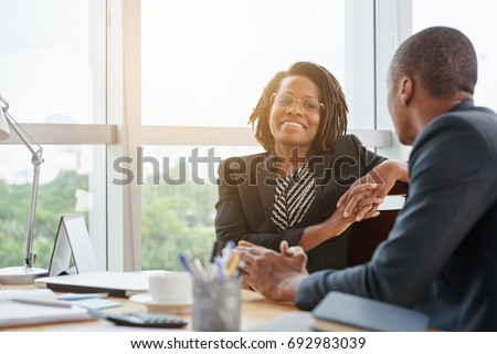 Beautiful smiling African-American business lady chatting with coworker