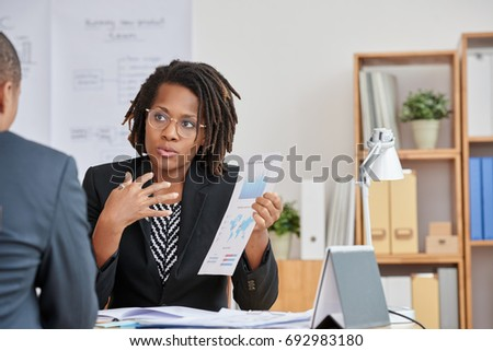 African-American business woman explaining results of her work to colleague #692983180