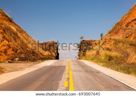 Road passing through narrow cutted rock with blue sky #693007645