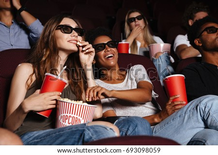 Picture of cheerful friends sitting in cinema watch film eating popcorn and drinking aerated sweet water. #693098059