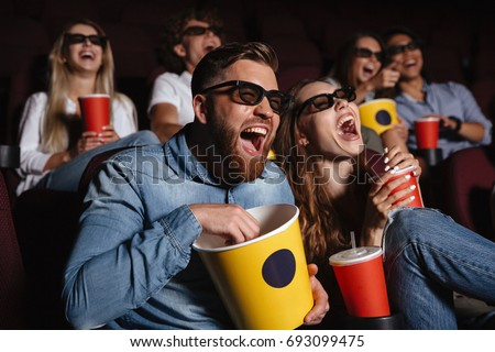 Image of laughing friends sitting in cinema watch film eating popcorn and drinking aerated sweet water. #693099475