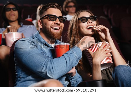 Picture of happy friends sitting in cinema watch film eating popcorn and drinking aerated sweet water. #693103291