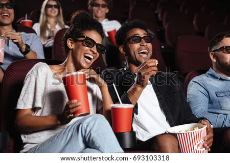 Picture of happy friends sitting in cinema watch film eating popcorn and drinking aerated sweet water. #693103318