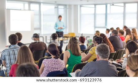 Business and entrepreneurship symposium. Speaker giving a talk at business meeting. Audience in conference hall. Rear view of unrecognized participant in audience. #693123976
