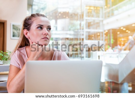 Young business woman working with laptop and thinking about future at open space office in modern interior #693161698