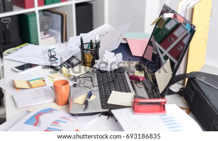 Messy and cluttered office desk Royalty-Free Stock Photo #693186835