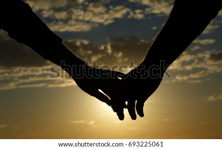Be hand in hand.  Silhouette of female and male hands connected together against the sky at sunset. vacation concept.Lovers silhouette. Magic moments of loving hearts.Young couple in love outdoor.    Royalty-Free Stock Photo #693225061
