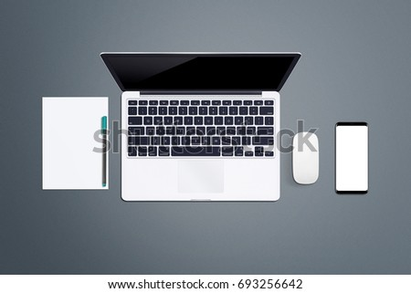 Gray desk office table with laptop, phone, mouse, paper and pen. Top view with copy space, flat lay #693256642