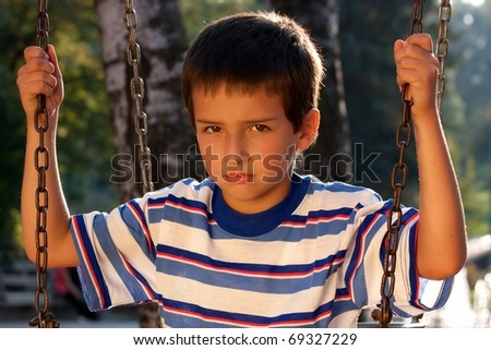 Portrait of little boy on swing playground outdoors - looking at the camera #69327229