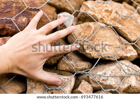 Man's hand on a stone wall #693477616