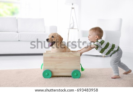 Cute child and Labrador Retriever playing with wooden toy cart at home #693483958