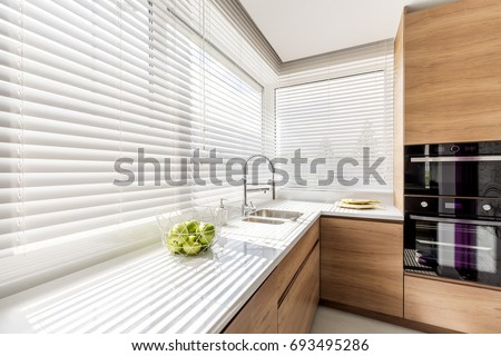 Modern bright kitchen interior with white horizontal window blinds, wooden cabinets with white countertop and household appliances Royalty-Free Stock Photo #693495286