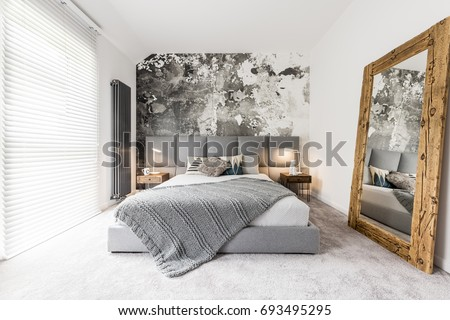King-size bed with gray square headboard, large rustic wooden mirror and textured wall in trendy minimalist apartment  #693495295