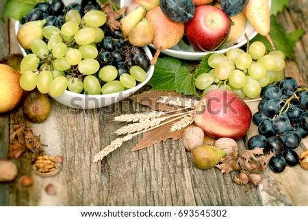 Fresh organic seasonal fruit, autumn fruit - autumn harvest on rustic table Royalty-Free Stock Photo #693545302