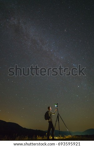 The man with a camera stand on the starry sky background. night time #693595921