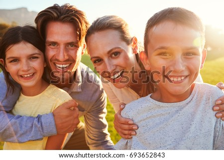 Portrait of happy white family embracing outdoors, backlit #693652843