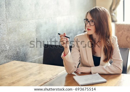 Young caucasian businesswoman with notebook and pen. Thinking woman in glasses in a cafe, copyspace. #693675514
