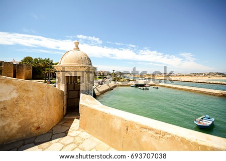 View from fortress Forte da Ponta da Bandeira in Lagos to waterfront with marina and old town, Algarve Portugal  #693707038