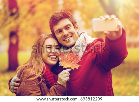 love, technology, relationship, family and people concept - smiling couple with maple leaf taking selfie by smartphone in autumn park