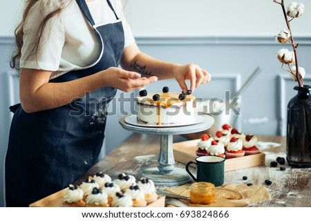 Pastry chef in the kitchen decorating a cake of chocolate,fruit,candies,Confectioner is decorating chocolate cake,cooking class, culinary, bakery, food and people concept Royalty-Free Stock Photo #693824866
