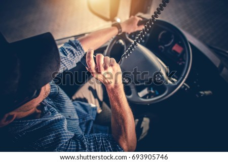 Semi Truck Driver Making Conversation with Other Truck Drivers Through CB Radio. #693905746