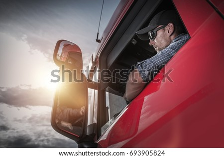 Red Semi Truck. Caucasian Truck Driver Preparing For the Next Destination.  Royalty-Free Stock Photo #693905824